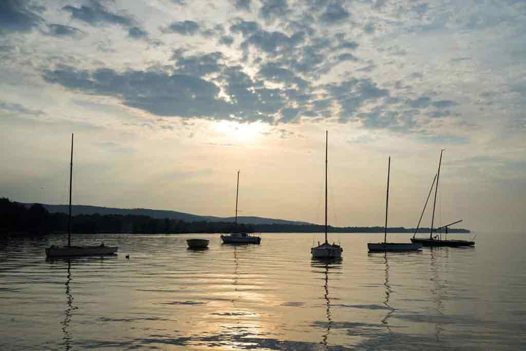 Plachetnice pokojne plávajú na pri pobreží Balatonu pred východom Slnka.