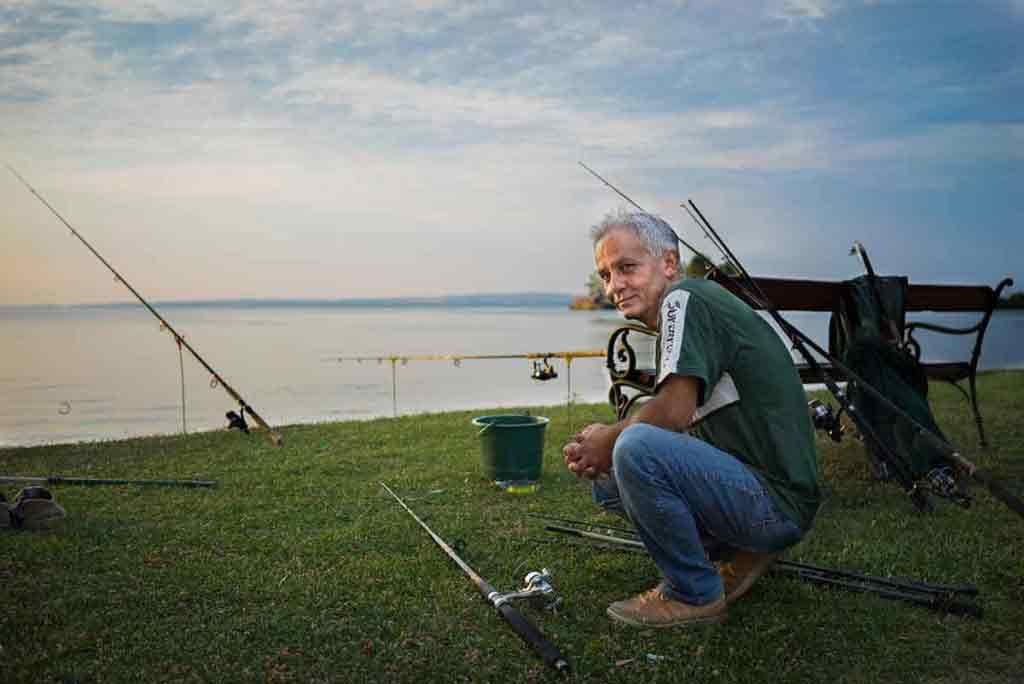 Rybári osídľujú pláže okolo Balatonu cez noc, po svitaní ich vystriedajú turisti.